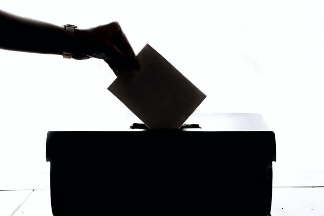 A silhouette of someone placing a voting card into a ballot box. The green party won many seats in French local elections on June 28 2020.