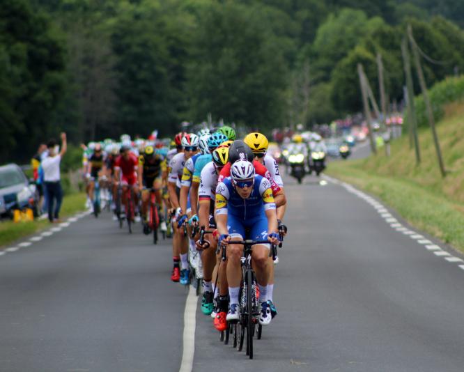 Men on bikes with the Tour de France pass through Dordogne, France.