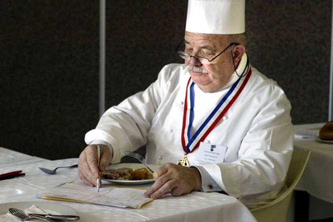 Pierre Troisgros makes notes as he sits in chef's whites, also wearing a French food medal. 'Last of great French chefs' Michelin-starred Pierre Troisgros dies age 92