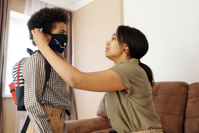 A mother puts a mask on her son. Covid France: Extended curfew expected but schools stay open