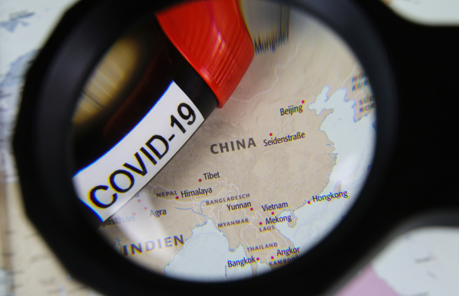View through magnifying glass on map with focus on China and blood sample vial covid-19. French scientists join group calling for inquiry into Covid origins