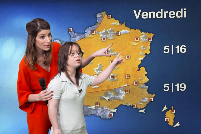 Woman in red and younger woman in white point to weather map of France