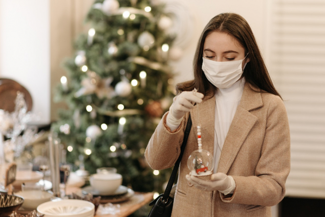 A woman looks at a Christmas decoration while wearing a mask. France rules out Christmas travel ban ahead of PM speech