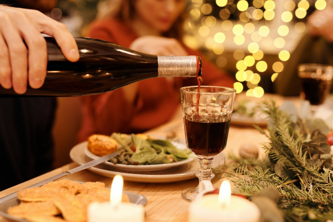 Wine is poured at a Christmas dinner table. Christmas Eve in France: No curfew but safety advice applies