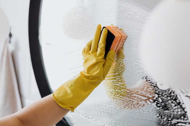 A woman cleaning a mirror with rubber gloves on. New cleaning product 'Toxi-Score' in France: Your FAQs