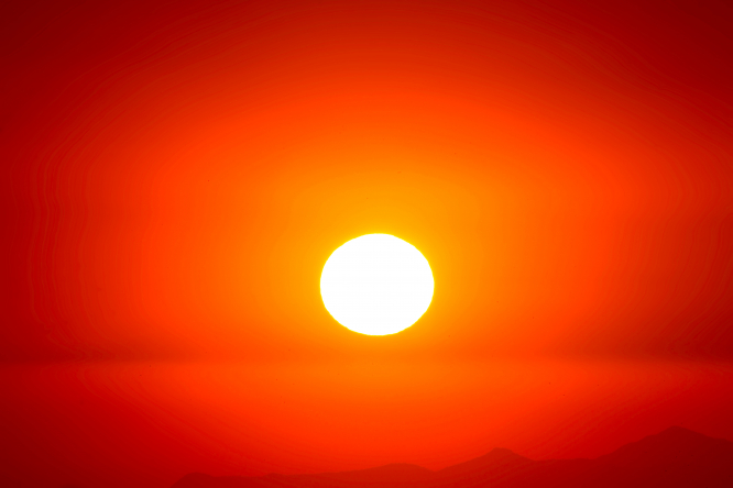 A close up image of the sun with with a red sky as the backdrop.