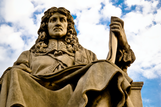 A statue of Colbert against a blue sky with clouds. The statue of the slave trader, which stands outside the Asemblée Nationale in Paris is drawing debate