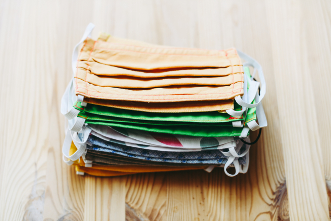 A stack of reusable masks on a table.