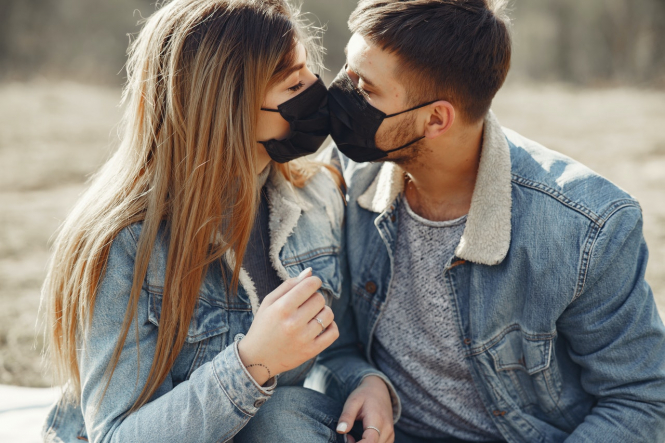 A couple kiss while wearing black face masks. France introduces Covid-19 travel waiver for unmarried couples separated by restrictions