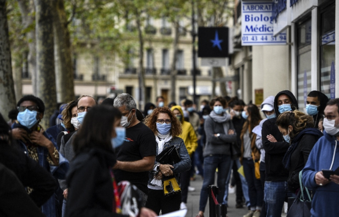 People waiting outside testing lab in Paris. Five-hour wait for Covid tests as France targets 1m per week