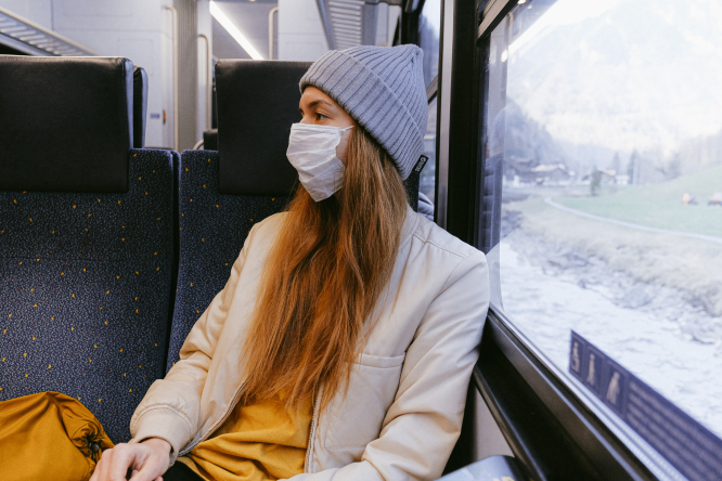 A woman wearing a mask sits in a train in winter. French train firm SNCF considers price capping after Covid