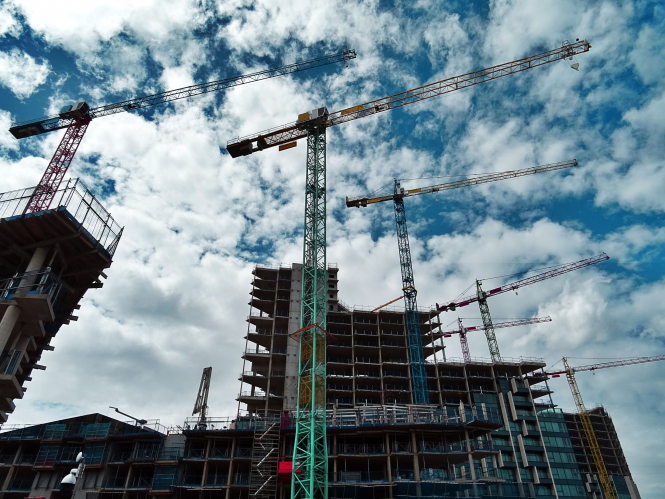 Three cranes on a building construction site. 60,000 French contracts have been cancelled as the Elite Insurance firm closes.