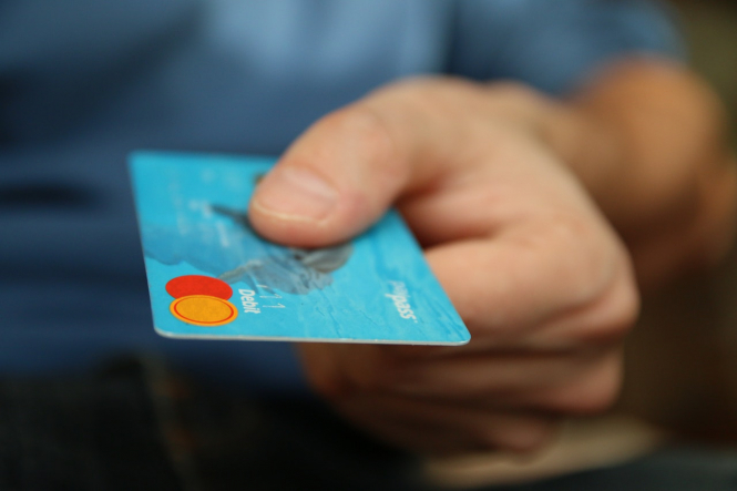 A man hands over a credit card. Fingerprint card payments instead of PIN are coming to France in autumn