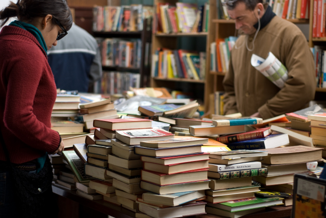 Customers browsing in bookshop. French State to pay delivery fees for bookshops in lockdown