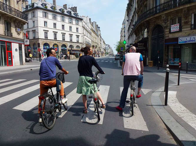 Three cyclists waiting at Paris crossroads. New road safety campaign for cyclists announced in France