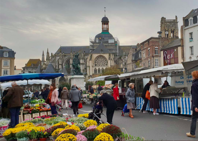 A market street with flowers and a church in the background. Dieppe market has been voted the 'most beautiful market' in France announced in 2020