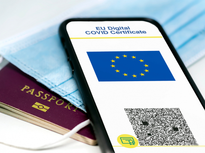 EU Digital COVID Certificate with the QR code on the screen of a mobile phone over a surgical mask and a passport.