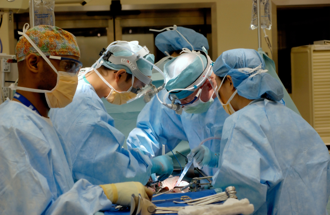 Doctors performing surgery. Paris hospitals cancel 40% of operations as Covid cases rise