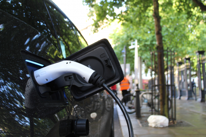 An electric car charging. President Macron yesterday announced that individuals could receive up to €12,000 to buy clean cars.