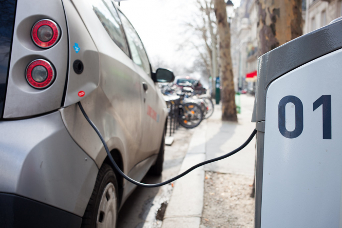 An electric car being charged at a charging point. France confirms €1,000 grant for second-hand electric cars
