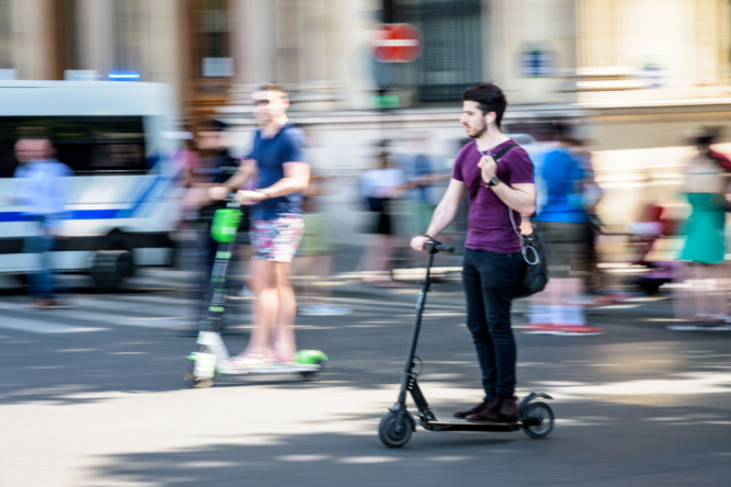 A man rides an electric scooter in Paris, with another man on another scooter behind. Electric scooters temporarily banned from Champs-Elysées