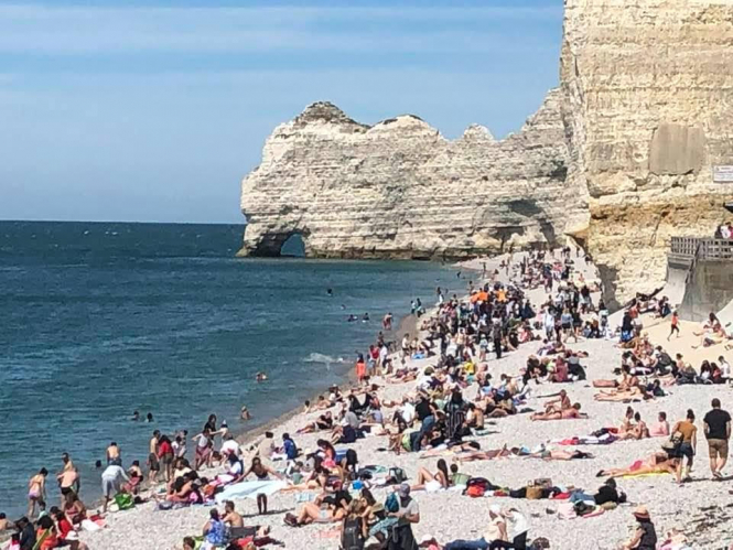 An image of the beach in Etretat, Normandy, full of tourists