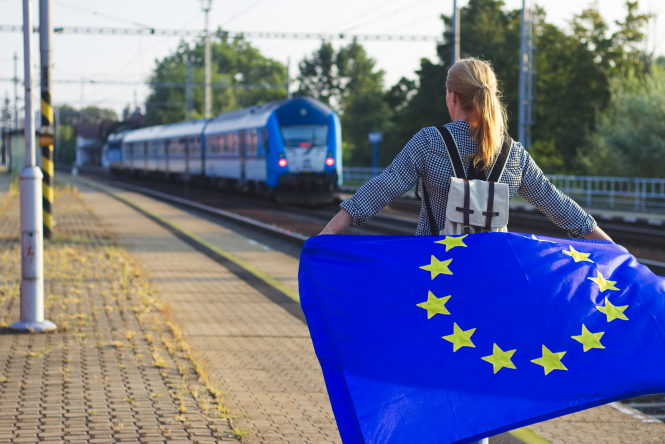 A person with an EU flag at a train station