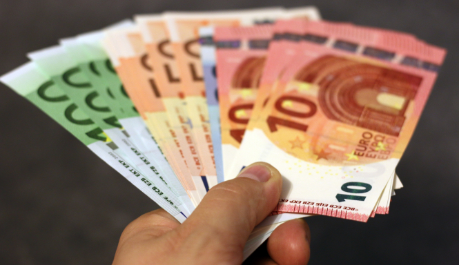 A picture of Euro bills in someones hand. Up to €8,000 is being made available for independent workers in France, from their retirement funds.