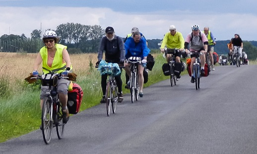 A large group of cycle tourists crest a hill