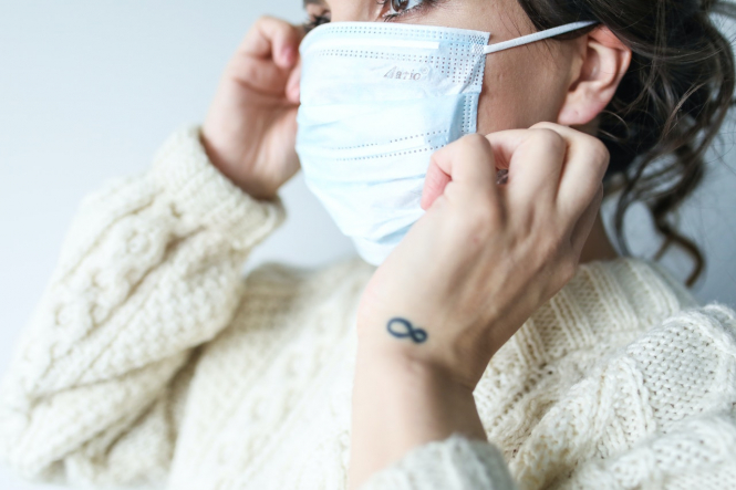 A woman adjusts a face mask. Masks are to become mandatory in public spaces indoors in France next week (not August 1)