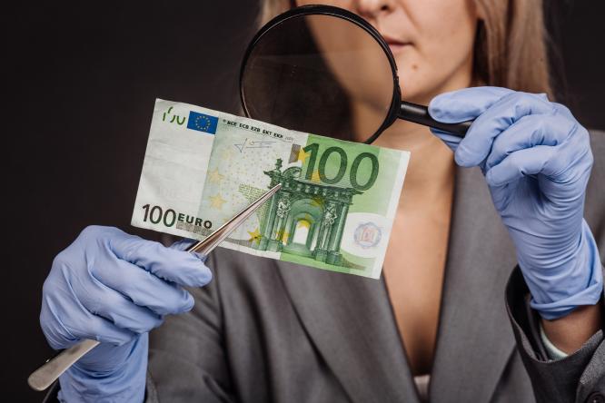 A woman inspects a €100 bill