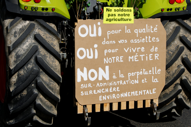 Protest poster in French on back of tractor with large wheels