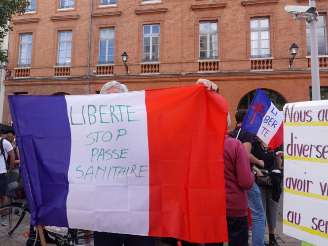 """A protester holds a French flag that has writing saying """"Freedom, Stop the health pass"""" on it. Sixth weekend of Covid health pass marches attracts 175,000 protesters"""