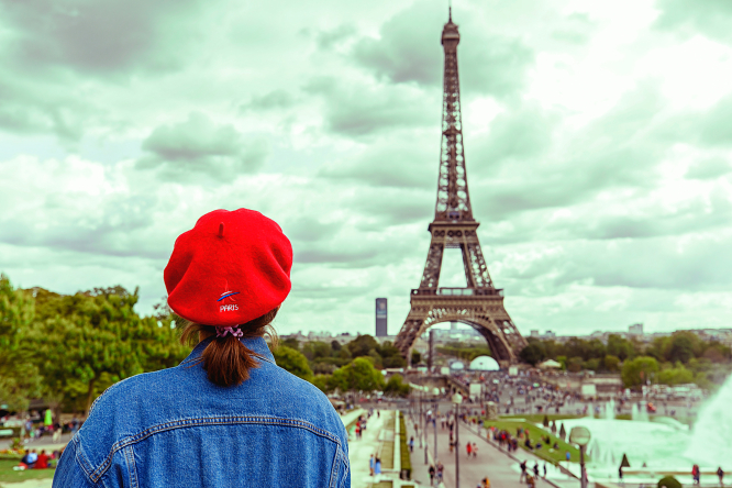 A woman looks at the Eiffel Tower in Paris