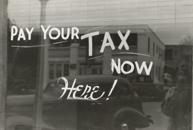 A vintage sign reads' Pay your tax now, here!'