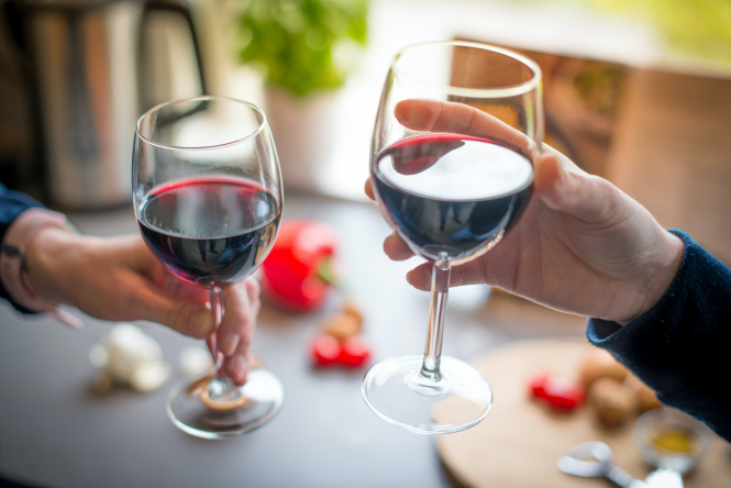 People with glasses of red wine. Lidl in France to sell AOP Bordeaux wine at €1.69 a bottle
