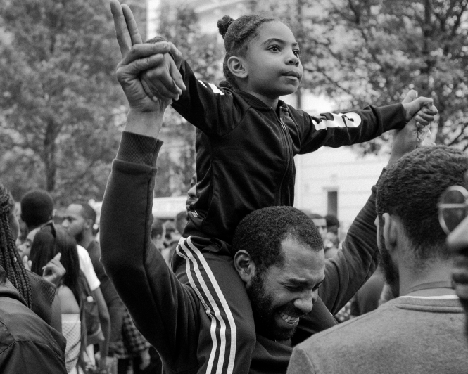 Young child sits on father's shoulders at Notting Hill Carnival, London. Article: Good news for fathers: paternity leave in France is set to double. Photo by Glodi Miessi / Unsplash
