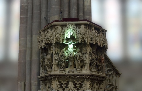 Green ray of light on Christ statue in Strasbourg Cathedral