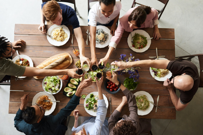 Group of people around table clinking glasses. French study finds social meals increase Covid contamination