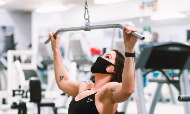 A woman wears a mask while exercising. French sports giant to launch exercise face masks