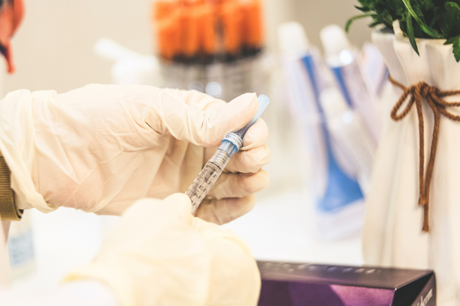 Hands in medical gloves holding vaccine. Covid vaccination in France to begin on Sunday