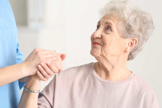 Older woman looks up at a nurse in a bright room. France pledges €240m for struggling at-home elderly care services
