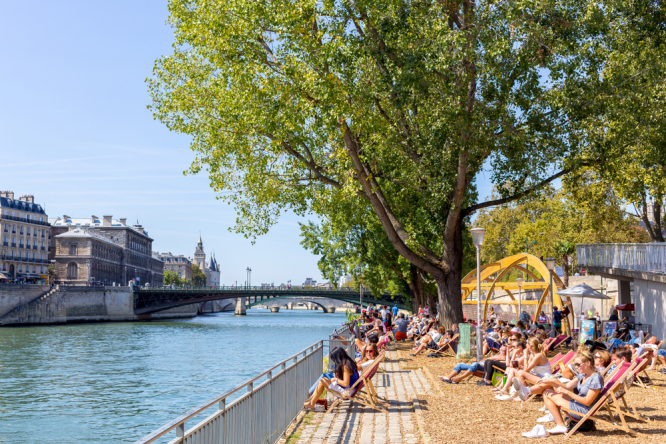 People in Paris enjoying a hot summer day at the Seine River. Innovative 'bench-fan' cools bottoms of people who sit on it in Paris