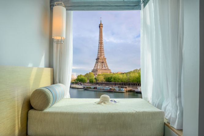 Hotel room window with Eiffel tower view. Paris hotels struggle as tourists opt for mountain and seaside breaks