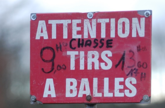 A sign saying: Attention tirs a balles (watch out, hunting with bullets). Hunting for large game permitted in France despite lockdown