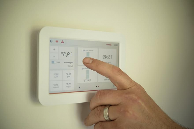 Man selects option on heating tablet in home.
