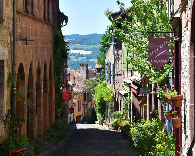 A cobbled street in Cordes-sur-Ciel, France, with a view of green hills.