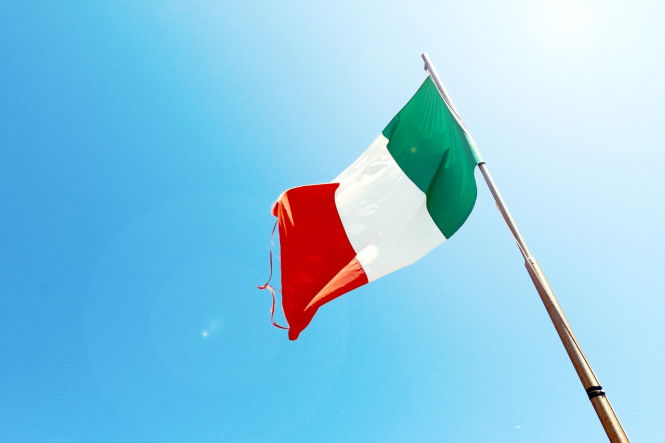 An Italian flag against a blue sky. Italy requires Covid tests for travellers from seven regions of France
