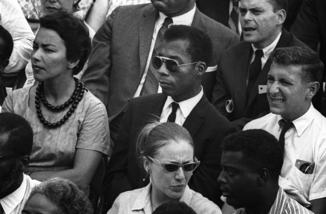 Man in sunglasses among a seated audience in black and white photo