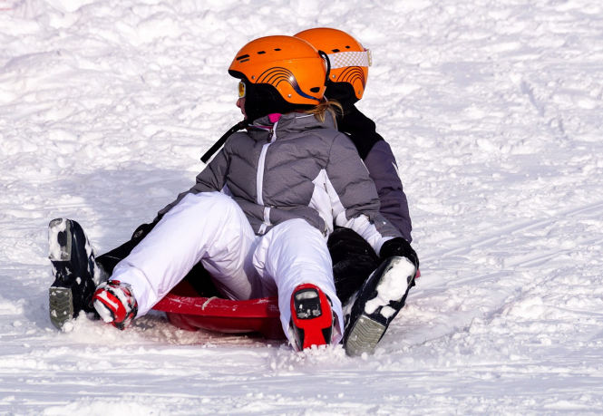 Two children sledding in the snow. February holidays in France still possible - so far